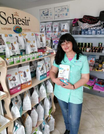 Elisaveta Dimitrova in front of dog and cat food products at MedinaVet's Pet store